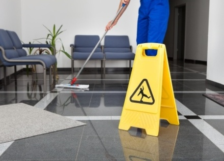 23345782 - close-up of man cleaning the floor with yellow wet floor sign